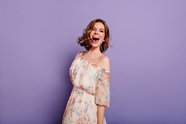 Sensual white woman in summer dress laughing on purple background