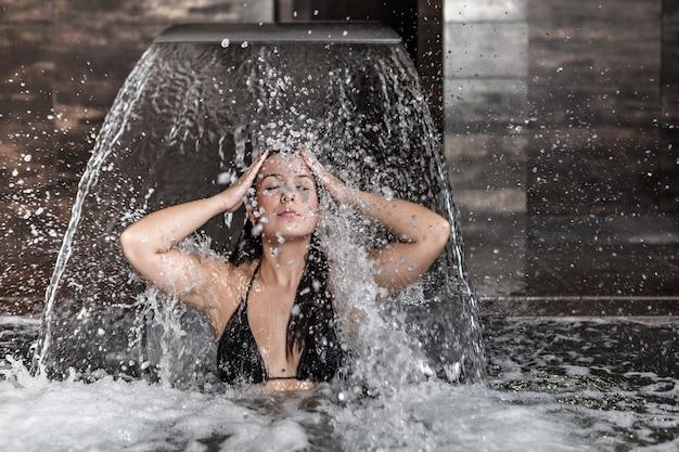 Чувственная женщина отдыхает под струей водопада