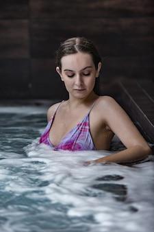 Чувственная женщина, наслаждающаяся гидротерапией в бассейне