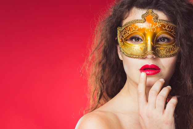 Sensual woman in golden carnival mask