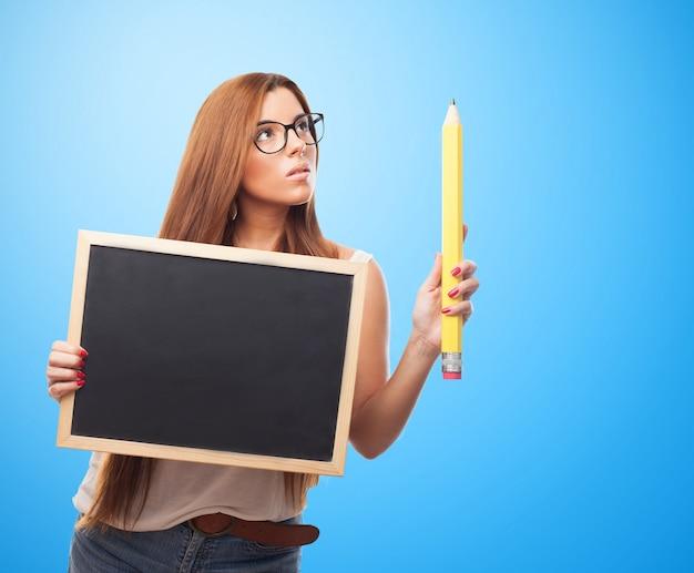 官能的な女性保持黒板や大きな鉛筆