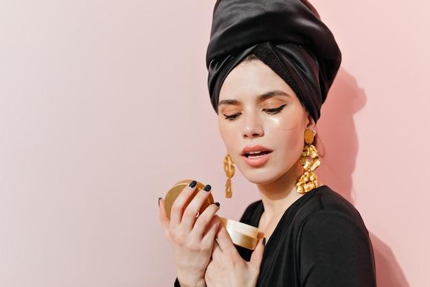 Sensual woman holding face cream
