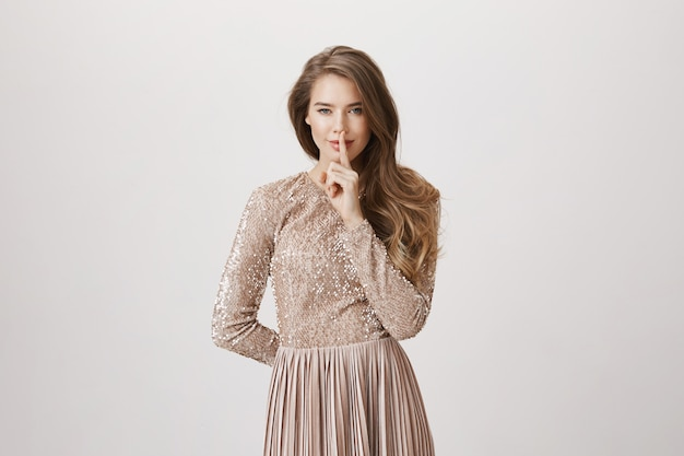 Sensual woman hush, press index finger to lips, wear evening dress