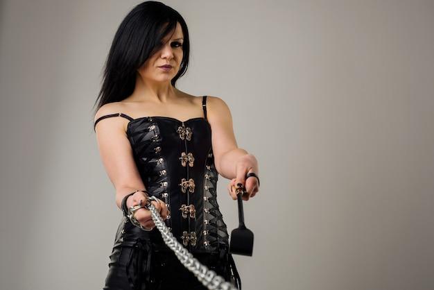 Чувственная женщина в черном кожаном корсете с цепочкой и хомутом в руке