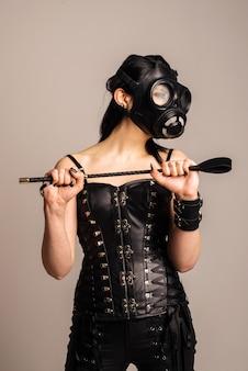 Чувственная женщина в черном кожаном корсете с противогазом и хлыстом в руке