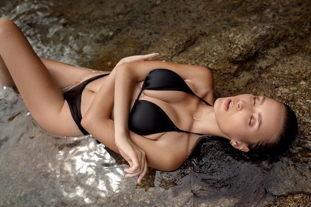 Чувственная женщина в черном купальнике, лежа на скалистом пляже. женщина моды с идеальной грудью
