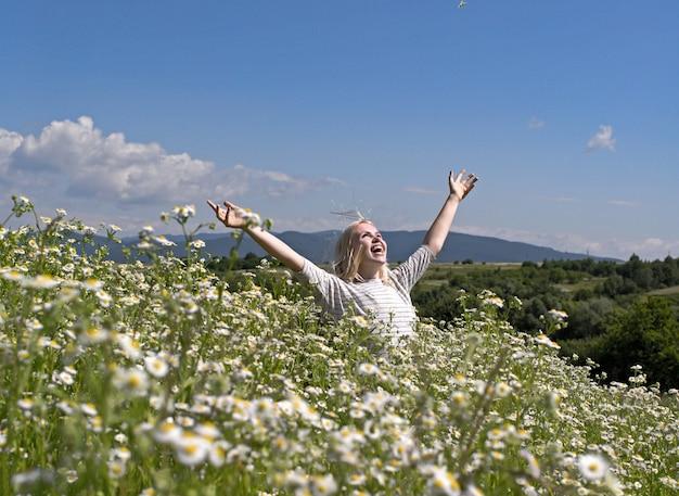 꽃이 만발한 꽃밭에서 관능적 인 여자 봄 여성의 날 어머니의 날 아름다움 봄 여자 카모마일 필드 여름 휴가 방황 스파