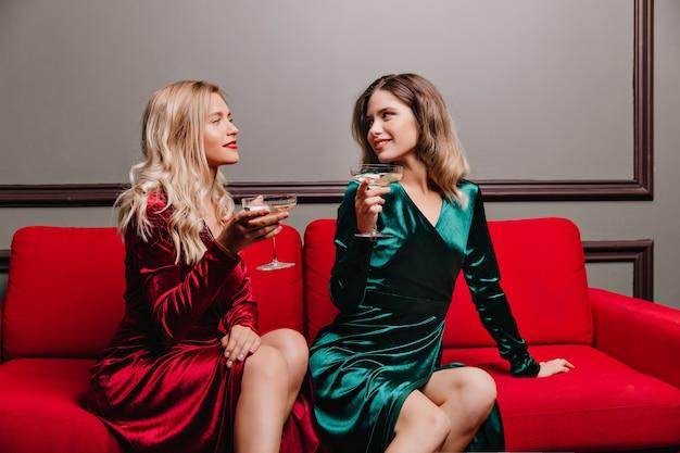 ワインのグラスを保持している緑のドレスの官能的な女性。シャンパンを話したり飲んだりする楽しい女の子。