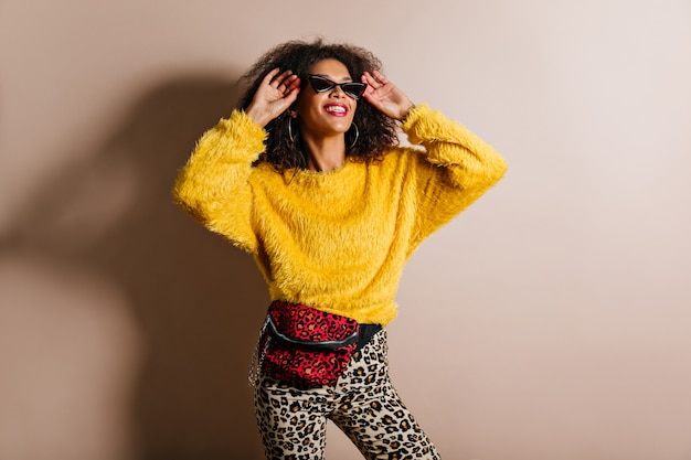 Чувственная женщина в модном желтом свитере смотрит вверх