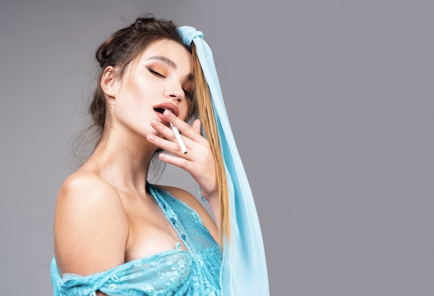 Sensual woman portrait. high fashion portrait of elegant woman in blue dress. studio shot of sensual woman on gray background.