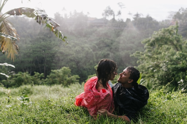 Sensual woman in raincoat posing on the grass with boyfriend. couple of travelers looking at each other while chilling after trekking.