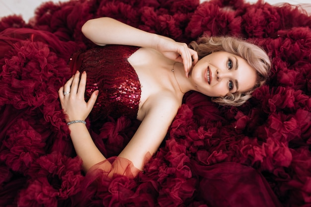 Sensual woman in red burgundi dress lies on the floor in bright room