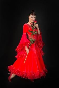 빨간 드레스에 어두운 배경 볼룸 댄서에 장미 꽃과 관능적인 여자 미소