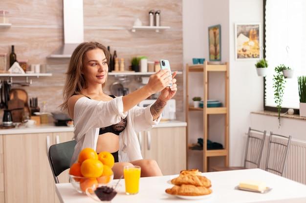 セクシーな下着を着て自宅のキッチンでスマートフォンを使用して写真を撮る官能的な女性。朝に魅力的な下着を着てスマートフォンを使用して入れ墨を持つ魅惑的な女性。