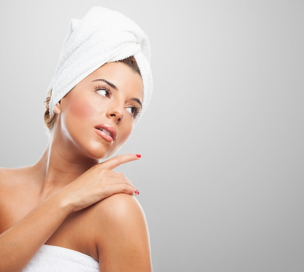 Sensual woman in towel on grey background