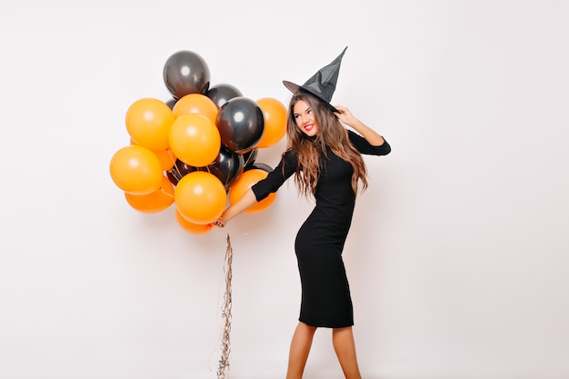 Sensual woman in witch costume waiting for halloween and holding orange balloons