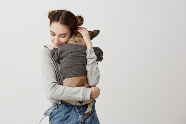 Sensual woman with childish hairstyle being mom of puppy while it lying on her shoulder with back. feeling of care and love expressing by female pet owner.