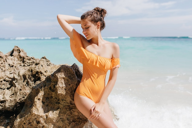 Donna sensuale con capelli scuri in posa vicino alla roccia del mare. affascinante modello femminile bianco in costume da bagno elegante in piedi sulla riva dell'oceano.