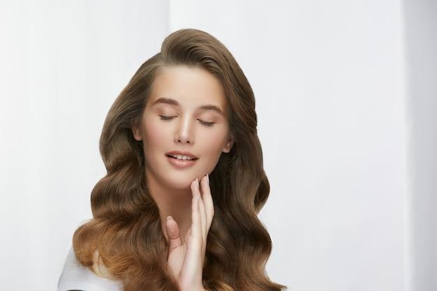 Чувственная женщина с роскошными длинными волосами, касаясь ее лица с закрытыми глазами