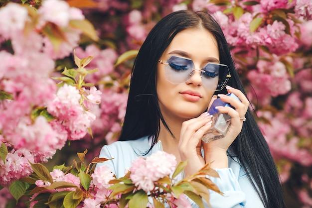 ピンクの花の香水瓶と官能的な女性。春のピンクの桜。春の日。トレンディなメガネでファッショナブルな女の子