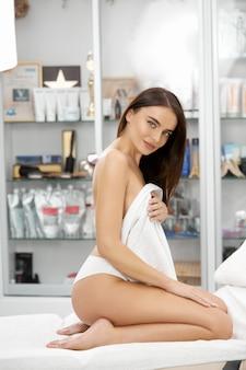 란제리를 입고 스파에서 수건으로 몸을 덮고 순수 부드럽고 신선한 피부를 가진 관능적 인 여자