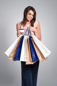 쇼핑백과 신용 카드를 가진 관능적 인 여자