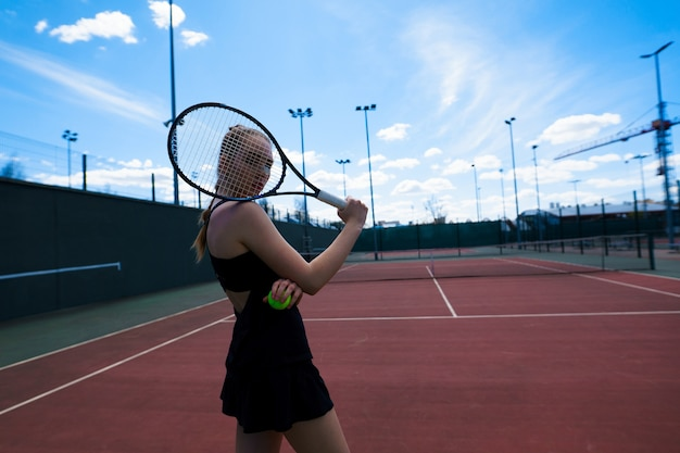 Sensual woman with tennis racket at net on lawn. activity, energy, power. sport training workout. wellness bodycare health