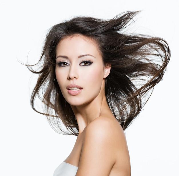 Sensuale giovane donna adulta con bei capelli lunghi castani, in posa isolato su bianco
