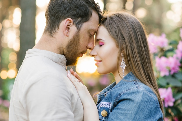 Sensual young couple enjoys tender warm pleasant kind moment of love having romantic date, affectionate beautiful man and woman touching foreheads caressing adoring each other in nature spring,