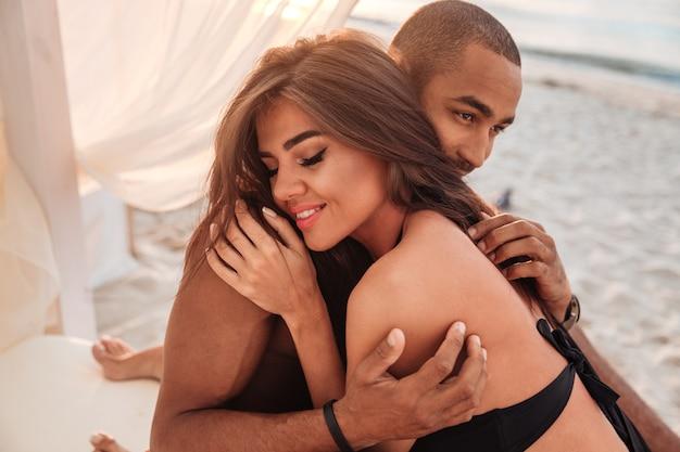 官能的な若いカップルがリラックスしてビーチで抱きしめる