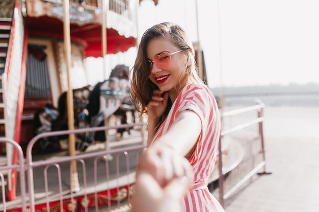 Чувственная молодая женская модель позирует возле карусели. открытый выстрел улыбающейся чудесной девушки, наслаждающейся днем в парке развлечений.