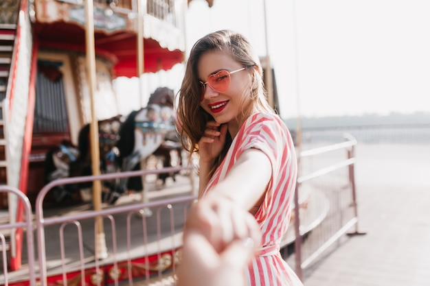 Sensual young female model posing near carousel. outdoor shot of smiling wonderful girl enjoying day in amusement park.