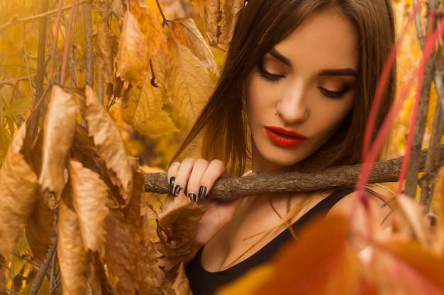 Чувственная молодая девушка с красными губами позирует в осенних листьях в лесу