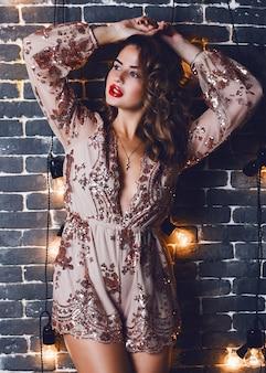 Sensuale giovane donna affascinante in posa sul muro di mattoni urbano con decorazioni di illuminazione