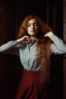 長い青々とした髪の官能的な若い赤い髪のモデル。暗い部屋でポーズをとる女性
