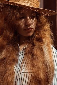 彼女の顔に影のある麦わら帽子の官能的な若い赤い髪の女性。クローズアップの肖像画