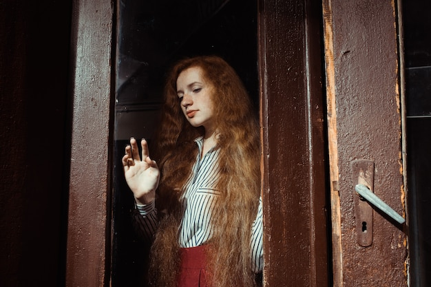 Sensual  young red haired woman with lush hair standing behind the glass