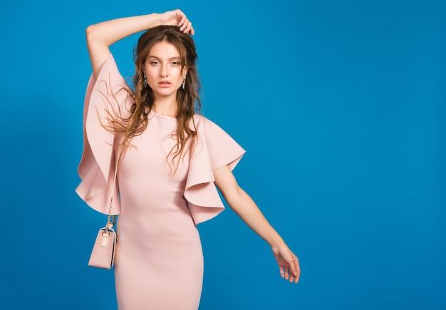핑크 럭셔리 드레스, 여름 패션 트렌드, 세련된 스타일, 블루 스튜디오 배경, 유행 핸드백을 들고 관능적 인 젊은 세련된 섹시한 여자