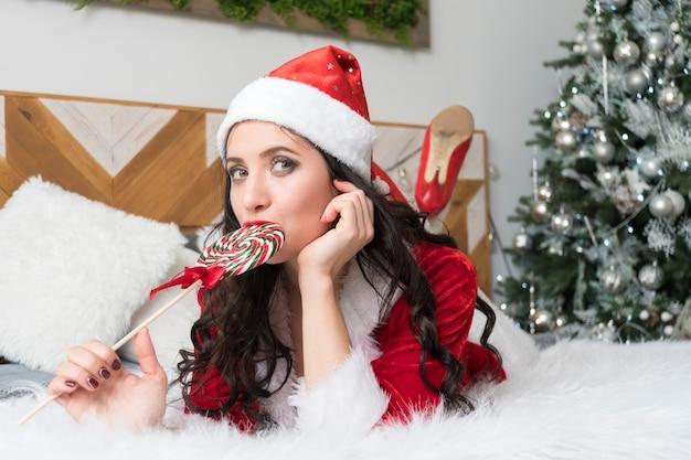 キャンディケインを噛む官能的な若い女性。赤いスーツのサンタの女の子は、ベッドに横たわっている窓の中で夢のように見えて、棒でロリポップを口に入れます