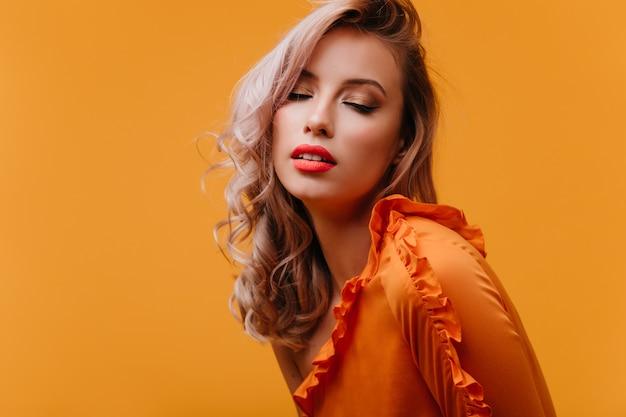 Sensuale giovane donna in abito luminoso in posa con gli occhi chiusi