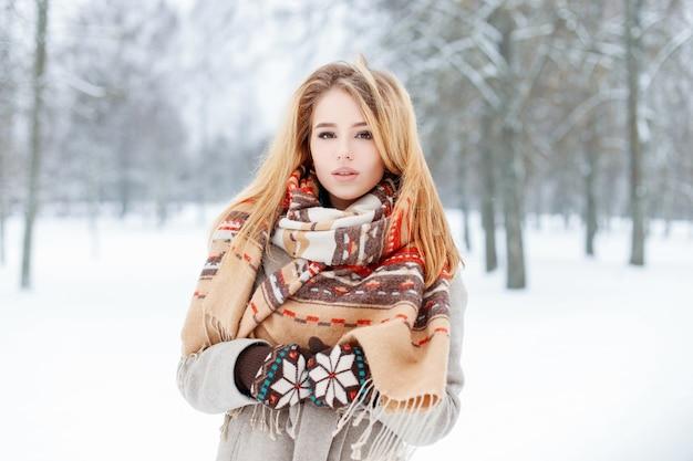 빈티지 모직 스카프가 달린 귀여운 니트 장갑에 세련된 회색 코트를 입은 관능적 인 젊은 여성이 겨울 추운 날 눈 덮인 숲에서 산책합니다. 매력적인 유행 소녀 모델.