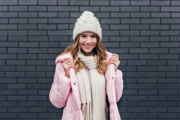 寒い日に歩き回る気分の良い官能的な若い女性。ニット帽でポーズをとる楽しいブロンドの女の子の屋外の肖像画。