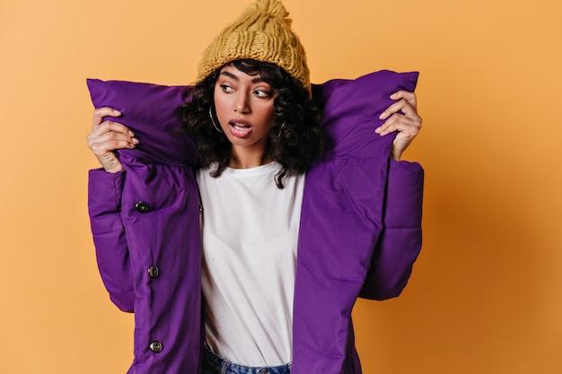 目をそらしている紫色のダウンジャケットの官能的な若い女性