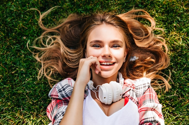 公園の地面でポーズをとる官能的な若い女性。草の上に横たわっているかわいい笑顔の女の子。
