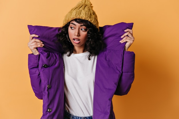 Sensual young woman in purple down jacket looking away