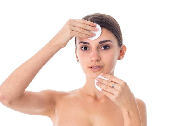 관능적 인 젊은 여자는 흰 벽에 고립 된 클렌징 코튼 패드로 그녀의 피부를 돌 봅니다.
