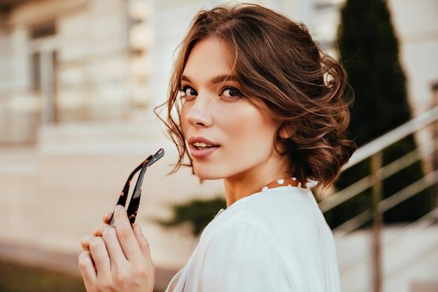 Giovane donna sensuale in camicetta bianca che osserva sopra la spalla. positiva ragazza elegante con i capelli corti in posa sulla strada.
