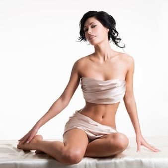 Чувственная молодая женщина с красивым телом в бежевом шелке над белой стеной