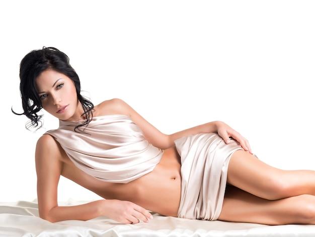 白い壁にベージュのシルクで美しいボディを持つ官能的な若い女性