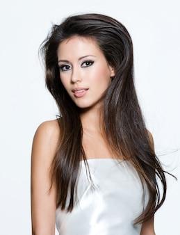Чувственная молодая женщина с красивыми длинными каштановыми волосами, позирует изолированной на белом